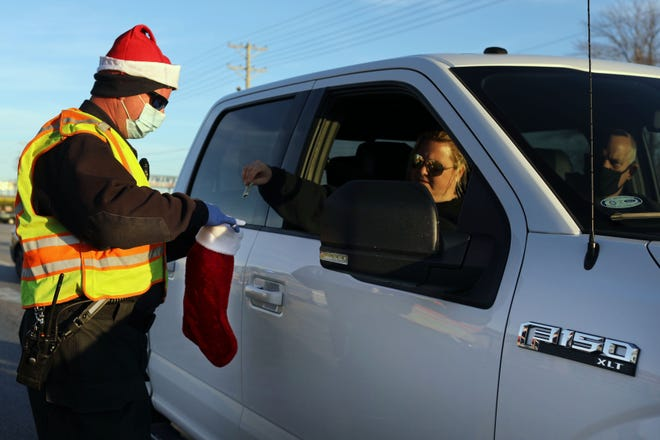 """West Burlington firefighter James Houghton collects donations Wednesday for the department's first-ever """"Fill the Stocking for the Kids!"""" fundraiser for the annual Toys for Tots collection, near the intersection of Broadway and Agency streets in West Burlington. Houghton and fellow firefighter Travis Sours collected more than $1,000 from passing motorists Wednesday. Firefighters will be back at it from 3 to 5 p.m. today near Division and Broadway streets collecting donations. More times and locations are planned over the next few weeks."""