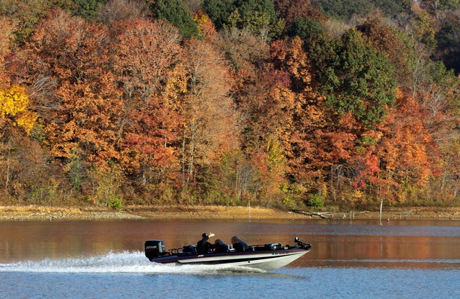 A fisherman heads out on Patoka Lake against a back drop of fall foliage in Celestine, Ind., Thursday, Oct. 14, 2010. (AP Photo/Michael Conroy)