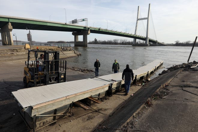 Scott Wehrle uses a forklift to remove a section of the dock Thursday at the North boat ramp along the Mississippi Riverfront. Wehrle and serval other city employees had removed the South boat ramp dock earlier in the day. The docks generally are removed from the river near the Thanksgiving holiday.