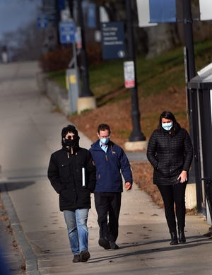 Walking on the University of New Hampshire campus in Durham, three people wear masks on a cold Wednesday afternoon.