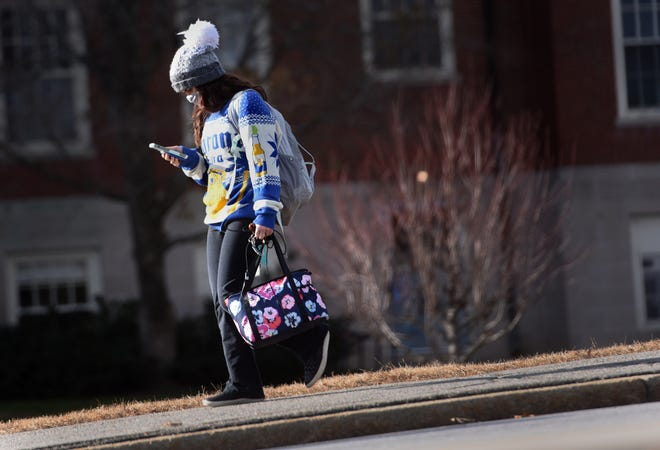A young woman checks her phone as she walks on the University of New Hampshire campus in Durham.