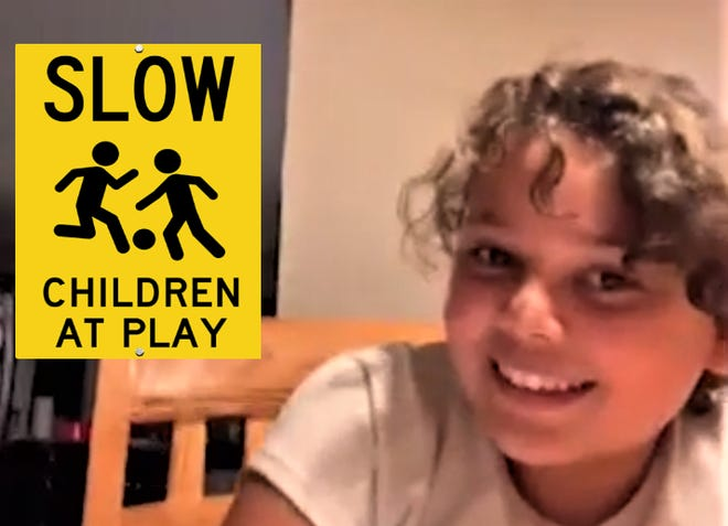 """Layla Arredondo, 11, of Grafton, wants to keep  the children in her Hilltop Street neighborhood safe from speeding cars so she asked the town to erect """"Slow Children at Play'' signs on Denholm, Hilltop and Fairlawn streets. The select board approved the request. She is pictured with a sample sign."""