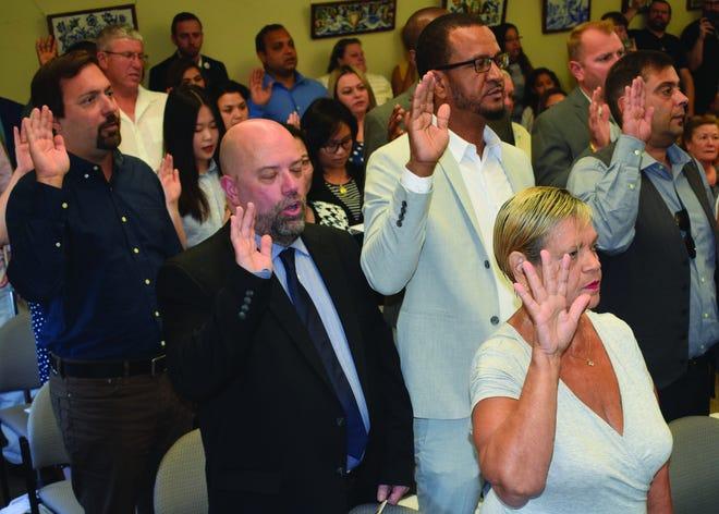 Futuros cidadãos norte-americanos levantam a mão para prestar o Juramento de Fidelidade durante uma cerimónia de naturalização realizada em 2019 no Centro de Assistência ao Imigrante em New Bedford.