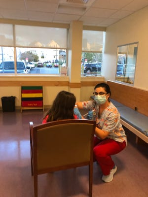 Nicole Sousa administers a flu shot to a patient at Pediatric Associates of Fall River.