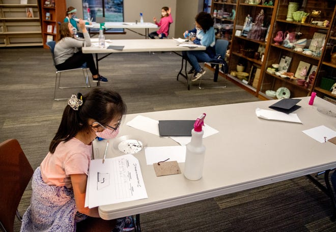 Brianna La, 9, keeps an eye on an earthworm as it crawls from a piece of sandpaper onto a smooth piece of paper during a 4-H GEMS program on earthworm behavior on Nov. 17 at the Morton Public Library.