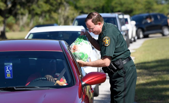 Polk Sheriff's Charities will give out up to 1,300 free Thanksgiving turkeys on Saturday at three sites to help those in need have a traditional holiday meal. Pictured here, Polk County Sheriff Grady Judd passes out turkeys in November 2018.