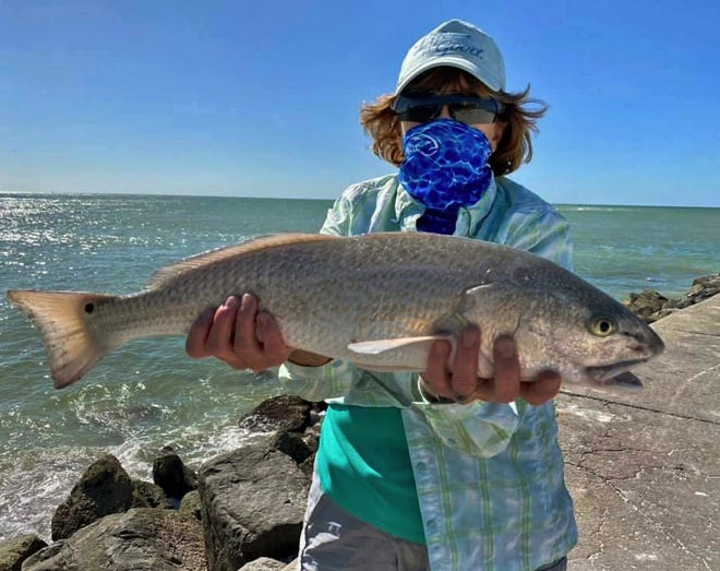 Eileen Kivlin of Halfmoon, New York, shows off a 23-inch redfish she caught on a live shrimp from the jetty at John's Pass in Madeira Beach on Wednesday.