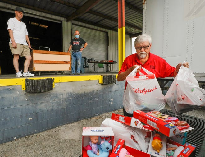 David Waller, Polk County coordinator for Toys for Tots, unloads toys that have been purchased at the organization's facility in Auburndale.