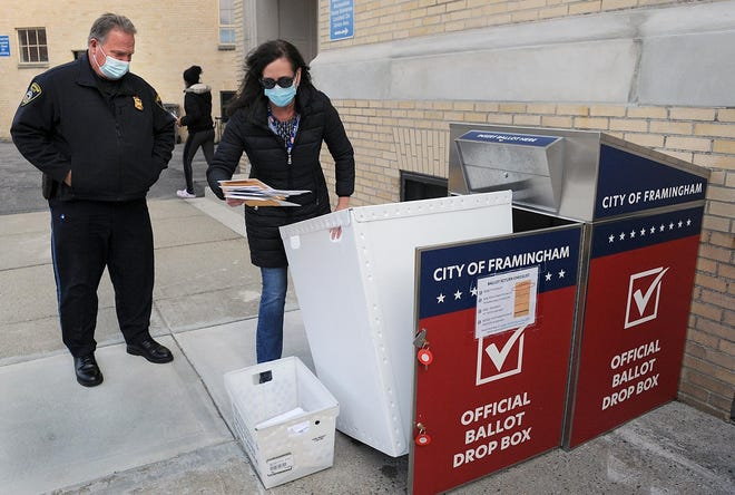 Framingham City Clerk Lisa Ferguson empties the official ballot drop box outside City Hall on the afternoon of Nov. 2. Looking on is Framingham police officer James Green.