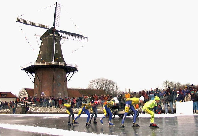 In this Saturday, Jan. 4, 1997, file image, skaters pass a windmill at the village of Birdaard, northern Netherlands, during the Elfstedentocht, or Eleven Towns Tour. The near-mythical Dutch speedskating race could fall victim to the coronavirus pandemic, even if the looming winter is cold enough to stage it for the first time in more than 20 years, organizers said Thursday.