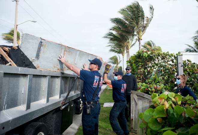 Members of Palm Beach fire rescue assist Friends of Palm Beach November 19, 2020, in removing debris from a boat that washed up on the north end of Palm Beach last week. The debris was loaded onto a truck from the town and hauled away.