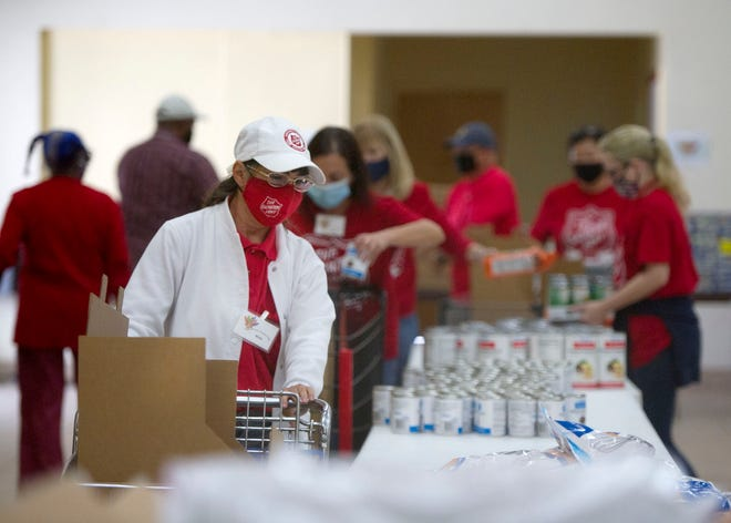 Volunteers pack boxes for local families for Thanksgiving with items donated by Laura and Isaac Perlmutter Foundation and the Nelson and the Claudia Peltz Family Foundation Thursday at the The Salvation Army Corps in West Palm Beach.