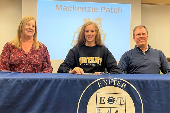 Exeter High School senior Mackenzie Patch, center, sits alongside her parents, Kristin and Jeff, after signing her National Letter of Intent to swim at Bryant University.