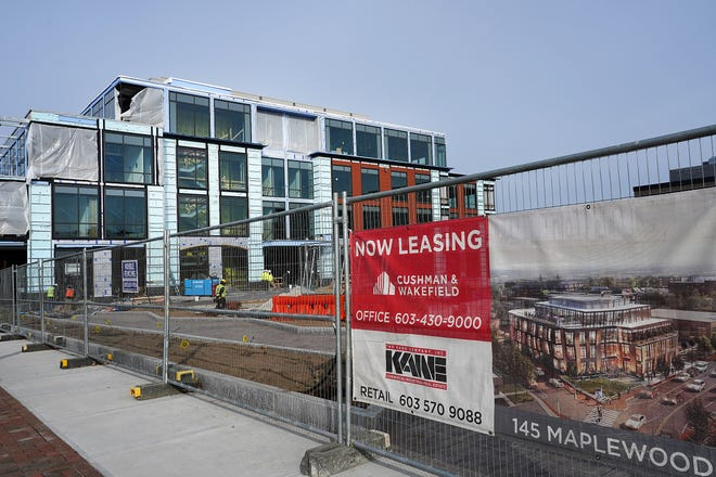Contractors work on a new 4-story office building located at 145 Maplewood Ave. in Portsmouth.