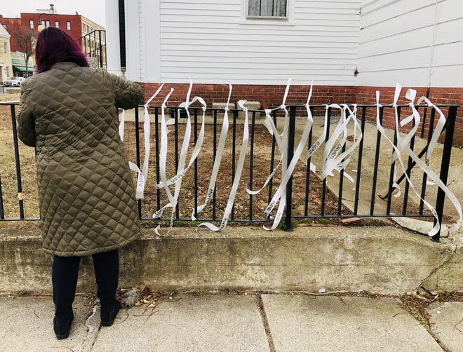 Ellen Fecteau ties white ribbons along the fence at North Parish Congregational Church on Main Street in Sanford on Thursday, Nov. 19, in honor of all Mainers who have died from COVID-19.