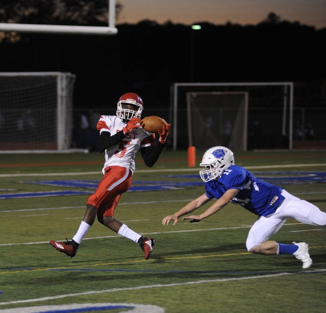 In this 2018 photo, Pocono Mountain East's Triston Hilliman brings in a pass for the touchdown as Pleasant Valley's Jack Stephens pursues him. The Cardinals host PV on Friday.