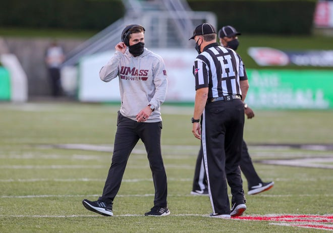 Massachusetts head coach Walt Bell talks with an official during a game against Marshall on Nov. 7 in Huntington, W. Va.