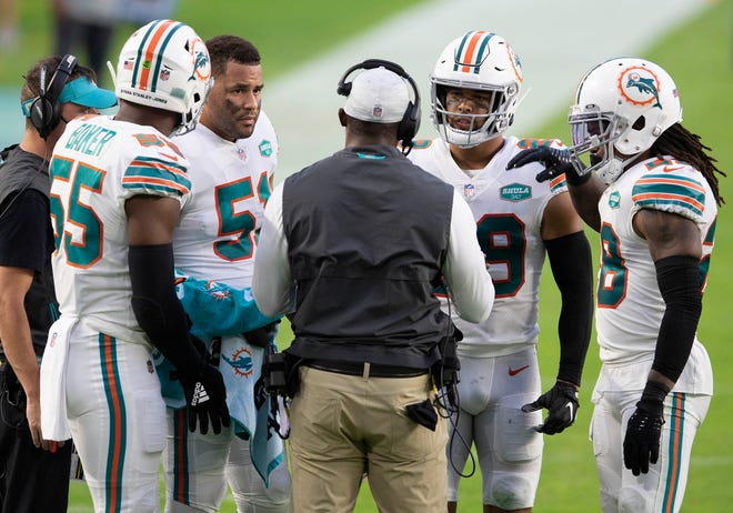Dolphins coach Brian Flores (back to camera) talks with defensive players Jerome Baker (55), Kamu Grugier-Hill (51), Brandon Jones (29) and Bobby McCain (28) during last Sunday's game against the Chargers at Hard Rock Stadium.