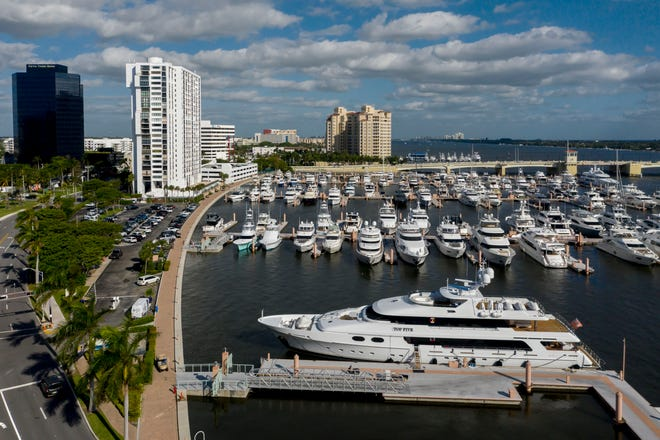 Yachts line the Intracoastal Waterway at the Palm Harbor Marina next to the white Waterview Towers condo building on Flagler Drive in downtown West Palm Beach. The parking lot at left and the sidewalk along the sea wall have been the subject of lawsuits dating to 2014.