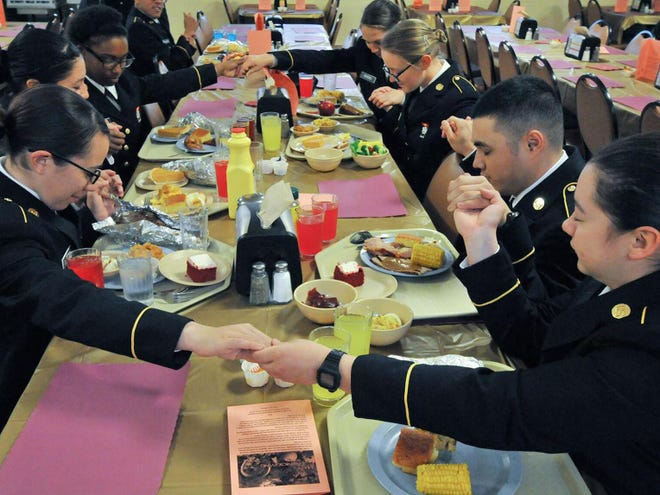 In this 2014 file photo, military students join hands to pray before the annial Thanksgiving Day meal at Fort Lee, Va. Because of COVID-19 restrictions, the post is limiting participation in this year's feast to students and some essential military personnel.