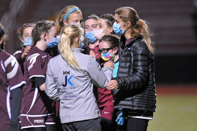 Goalkeeper Annelise Demers (tie-dye mask) gets some love from her teammates following Tuesday's 2-0 loss to West Warwick in the D-II quarterfinals. Demers had been the scorekeeper for the Crusaders until the varsity team's quarantine pulled her from mock trial and into the net.