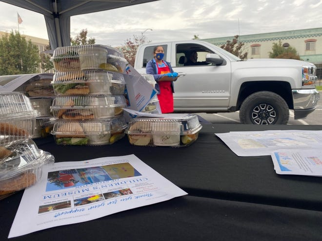 More than 200 supporters of the Children's Museum of Stockton drive through its parking lot at 402 W. Weber Ave. in downtown Stockton on Tuesday to pick up food during its annual Fall Luncheon fundraiser. The museum is temporarily closed due to the COVID-19 pandemic.