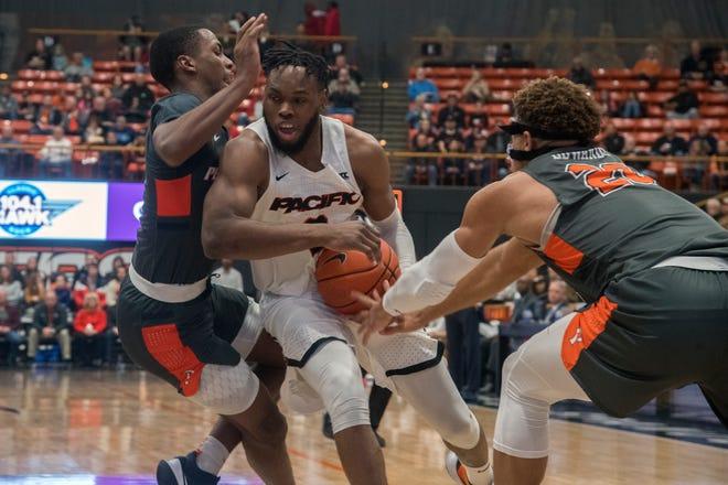 Pacific's Jahlil Tripp, center, drives between Pepperdine's Sedrick Altman, left, and Kameron Edwards  during a WCC men's basketball game at UOP's Spanos Center in Stockton. [CLIFFORD OTO/STOCKTON RECORD FILES]