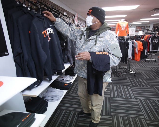 Jim Hendricks, a 1984 graduate of Washington High School, shops for Tiger gear at Simon Says Promotions The Tiger Store in downtown Massillon. Even though fans might not be at state championship game, they will be cheering on the football team.