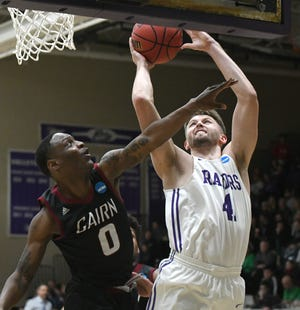 Mount Union's Logan Hill pushes through a foul from Cairn's Dashaun Cain to score in an NCAA Division III tournament first round game last season. (CantonRep.com / Ray Stewart)