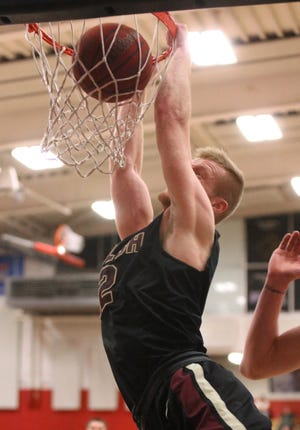 Walsh's Caleb Canter (12) dunks the ball during a game against Malone last season.