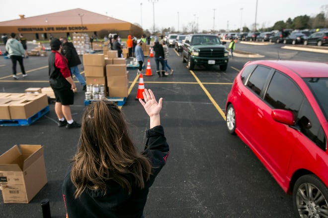 City First Leadership College student Jenna Stack directs traffic during the church's pre-Thanksgiving drive-thru food distribution event Nov. 19 at City First Church, 5950 Spring Creek Road, in Rockford. A similar event is scheduled for Thursday.