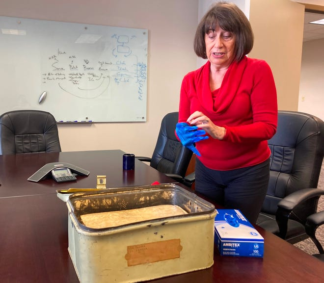 Susan Parker, historian for the St. Johns County clerk of court and comptroller, puts on a glove as she prepares to review a collection of documents from the early 1800s.