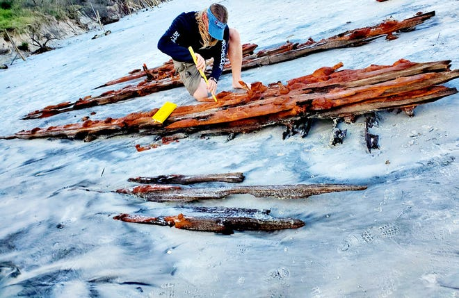 Chuck Meide, director of the Lighthouse Archeological Maritime Program in St. Augustine, takes measurements of the shipwreck that surfaced near Crescent Beach Saturday.