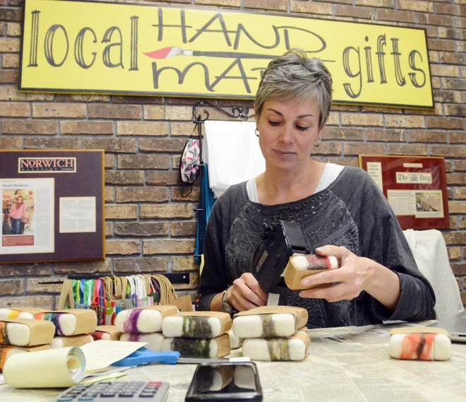 Erica Sullivan-Corbett, owner of Small Potatoes Crafts & Gifts in Norwich, prices soap wrapped in wool Thursday. [John Shishmanian/ NorwichBulletin.com]