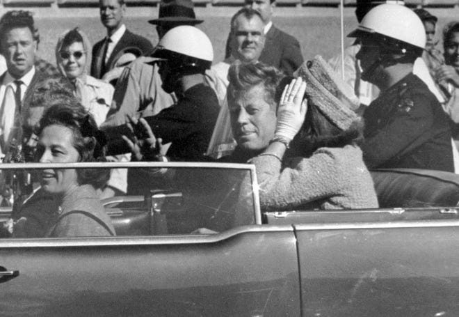 In this Nov. 22, 1963, file photo, President John F. Kennedy waves from his car in a motorcade in Dallas. Riding with Kennedy are First Lady Jacqueline Kennedy, right, Nellie Connally, second from left, and her husband, Texas Gov. John Connally, far left.