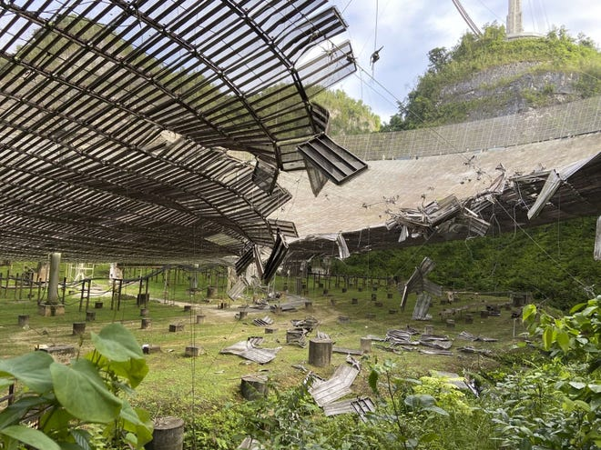 In this Aug. 11  file photo, provided by the Arecibo Observatory, shows the damage done by a broken cable that supported a metal platform, creating a 100-foot gash to the radio telescope's reflector dish in Arecibo, Puerto Rico.