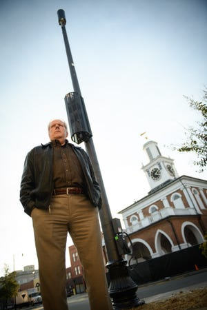 Del Crawford and other downtown business owners have sued a cellphone company to stop it from installing a 40-foot cell pole across the street from the Market House. The company erected it in front of The Sweet Palate at 101 Person St.
