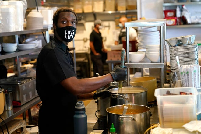 Kinoy Miller prepares food at the Love Life Cafe on Oct. 29 in the Wynwood neighborhood of Miami.
