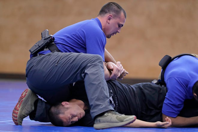 A law enforcement instructor restrains a fellow instructor during a demonstration on take-down and restraint techniques.
