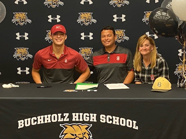 Buchholz High baseball player Brett Blair (left) who signed a national letter of intent with Stanford on Thursday, shares the moment with his father,  Dave, and mother, Christy, at the school.