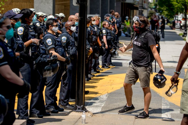 A man questions a line of police officers at Black Lives Matter Plaza in Washington on June 23.