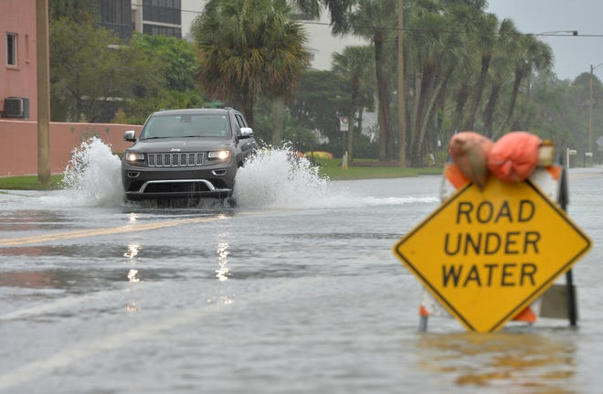 A vehicle drives through a flooded road in Sarasota on Nov. 11 as Hurricane Eta churned offshore in the Gulf of Mexico.
