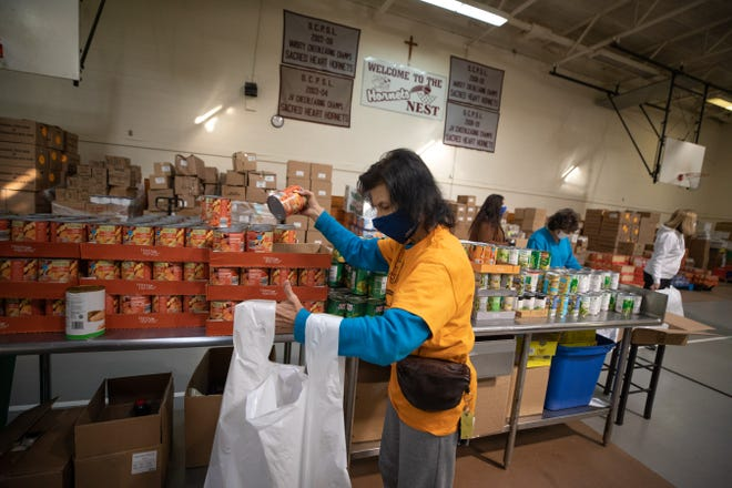 Volunteer Linda Jansen packs bags of food for Loaves and Fishes' Thanksgiving food distribution in Newburgh, NY on November 19, 2020.