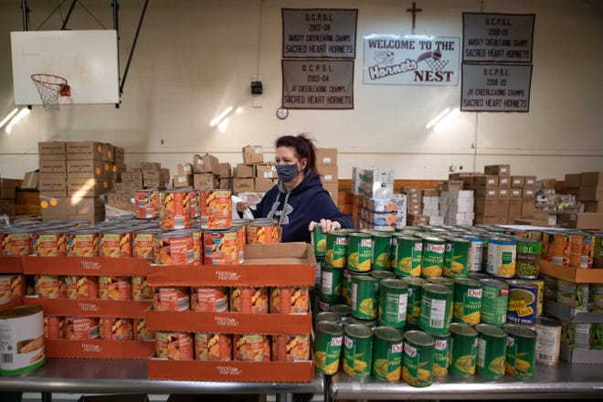Volunteer Ann Simoni packs bags of food for Loaves and Fishes' Thanksgiving food distribution in Newburgh, NY on November 19, 2020.