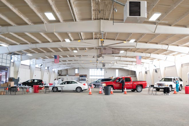 Vehicles line up in the Livestock Pavilion on Thursday at the Colorado State Fairgrounds as COVID-19 tests are being administered.