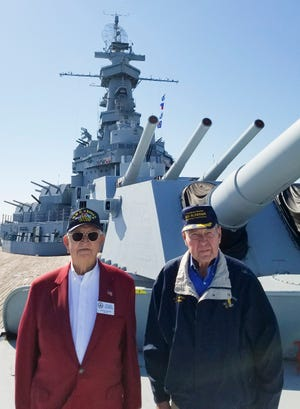 Commander Lee Hallman, U.S. Navy, retired, and Gary Fitts, both members of the USS Alabama Battleship Commission are seen standing beneath the ship's 16 inch main guns. Both men are from Tuscaloosa. [Photo Courtesy General Janet Cobb]