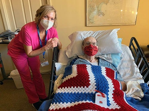 U.S. Air Force veteran Robert Riley, of Peabody, accepts a Veterans Day gift of a handmade patriotic afghan from his Care Dimensions hospice nurse Jennifer Goodrow.
