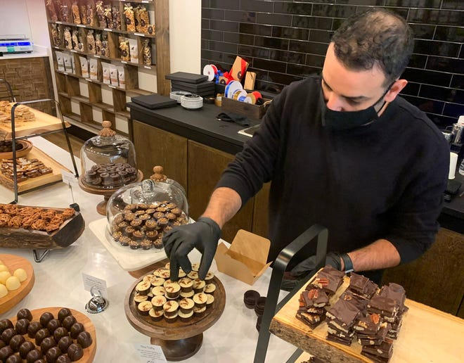 Leo Baez, owner of coffee and chocolate shop Cacao which just opened in Newton Highlands, gathered some chai truffles for a customer on Nov. 18.