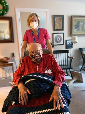 U.S. Army Air Corps veteran Roger Wootton, of Peabody, accepts a Veterans Day gift of a handmade patriotic afghan from his Care Dimensions hospice nurse Jennifer Goodrow.