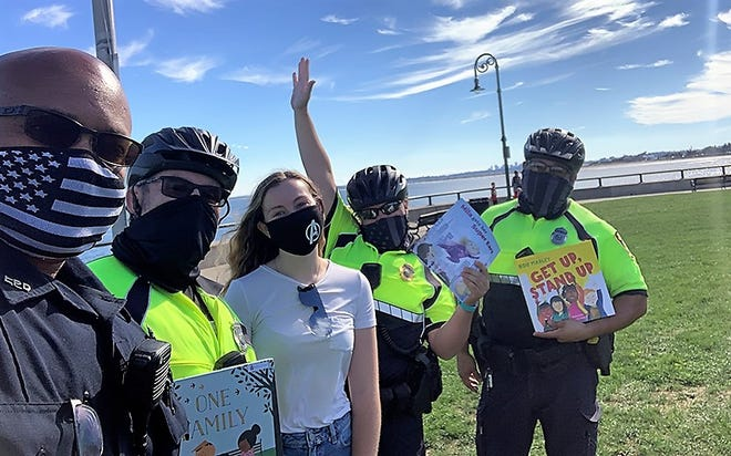 """Marbleheader Jenna McCarriston (center) at Red Rock Park with a few of the Lynn Police Officers that took part in her """"Badges & Books"""" internship project."""